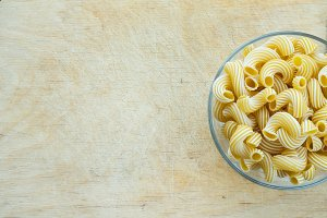 macaroni rigati Glass bowl with pasta on a wooden board with a side. Close-up view from the top. Free space for text.