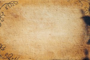 A wooden board with wrinkled colors and a drawing caused. Textured background view from the top. Free space for text.