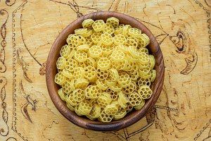 Macaroni ruote pasta in a wooden bowl on a wood-cut wooden plank, textured background, in the center close-up from the top.