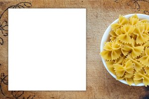 farfalle macaroni pasta in a white bowl on a cutting wooden board, textured background with a side. Close-up with the top. White space for text and ideas.
