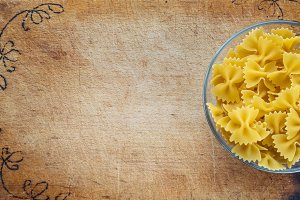 farfalle macaroni pasta in a glass cup on a cutting wooden board, textured background with a side. Close-up with the top. Free space for text.