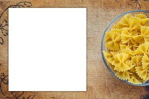 farfalle macaroni pasta in a glass cup on a cutting wooden board, textured background with a side. Close-up with the top. Free space for text. White space for text and ideas.