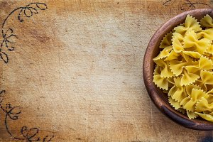 farfalle macaroni pasta in a wooden bowl on a cutting wooden board, texture background with a side. Close-up with the top. Free space for text.
