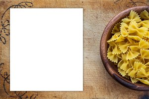 farfalle macaroni pasta in a wooden bowl on a cutting wooden board, texture background with a side. Close-up with the top. White space for text and ideas.