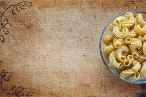 macaroni rigati pasta in a glass cup on a cutting wooden board, textured background with a side. Close-up with the top. Free space for text.