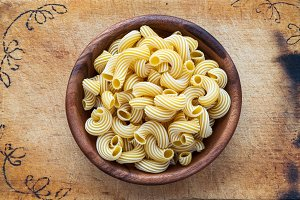 macaroni rigati pasta in a wooden bowl on a wooden cutting board decorated with a textured background, in the center close-up from the top.