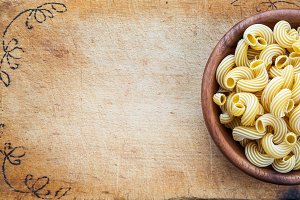 macaroni rigati pasta in a wooden bowl on a cutting wooden plaque, texture background with a side. Close-up with the top. Free space for text.