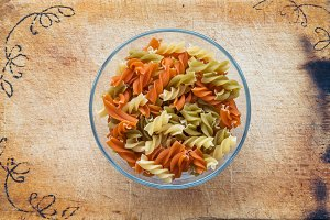 Multicolor spiral macaroni pasta in a glass bowl on a wooden cutting board decorated with a textured background, in the center close-up from the top.