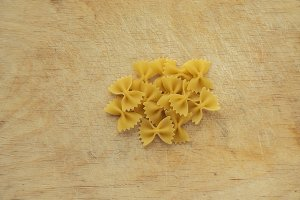 farfalle macaroni background with pasta on wooden board background. A view from the top, a close-up of a texture.