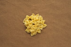 farfalle macaroni A handful of macaroni on a rustic brown textured background. A view from the top, a close-up of a texture.