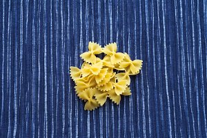 farfalle macaroni A handful of macaroni on a rustic striped white blue textured background. A view from the top, a close-up of a texture.
