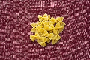 farfalle macaroni A handful of macaroni on a rustic red-brown textured background. A view from the top, a close-up of a texture.