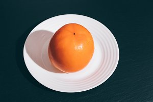 Orange persimmon on a white plate