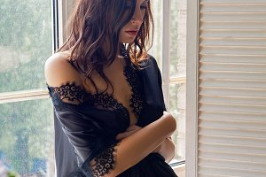 sexy brunette girl in a silk black robe sits