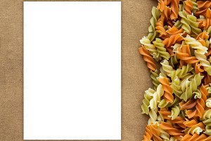 Multicolor spiral macaroni Beautiful decomposition pasta with law, the right to a rustic brown textural background. White space for text and ideas.