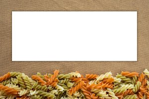 Multicolor spiral macaroni Beautiful decomposed pasta from the bottom on a rustic brown textured background. White space for text and ideas.