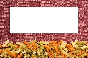 Multicolor spiral macaroni Beautiful decomposed pasta from the bottom on a rustic red-brown textured background. White space for text and ideas.