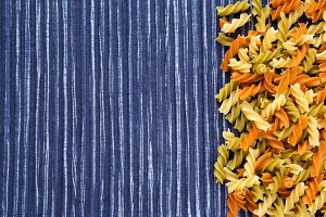 Multicolor spiral macaroni Beautiful decomposed pasta with the right, on its side in a rustic striped blue against a white textured background. Free space for text.
