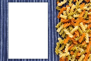 Multicolor spiral macaroni Beautiful decomposed pasta with the right, on its side in a rustic striped blue against a white textured background. White space for text and ideas.