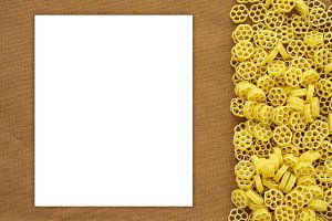Macaroni ruote Beautiful decomposed pasta with the right, on its side on a rustic brown textured background. Close-up view from the top. White space for text and ideas.