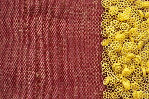 Macaroni ruote Beautiful decomposed pasta with the right, on its side on a rustic red-brown textured background. Close-up view from the top. Free space for text.