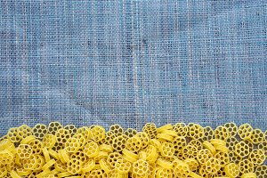 Macaroni ruote Beautiful decomposed pasta with a bottom on a rustic blue knitted sack texture. Close-up view from the top. Free space for text.