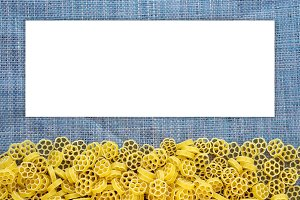 Macaroni ruote Beautiful decomposed pasta with a bottom on a rustic blue knitted sack texture. Close-up view from the top. White space for text and ideas.