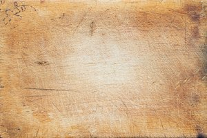 A textured wooden cutting board. Close-up view from top. Free space for text.