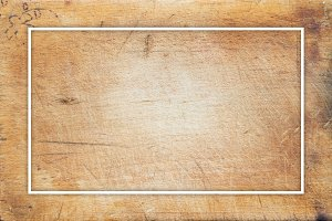 A textured wooden cutting board. Close-up view from the top. Free space for text. White frame for text.
