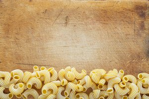 Macaroni rigati Beautiful decomposed pasta with a bottom on a wooden plank texture background. Close-up view from the top. Free space for text.