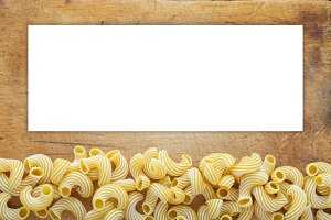 Macaroni rigati Beautiful decomposed pasta with a bottom on a wooden plank texture background. Close-up view from the top. White space for text and ideas.