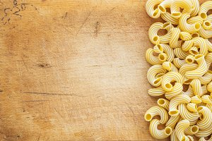 Macaroni rigati Beautiful laid out pasta with the right, side on a wooden plank texture background. Close-up view from the top. Free space for text.