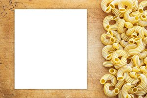 Macaroni rigati Beautiful laid out pasta with the right, side on a wooden plank texture background. Close-up view from the top. White space for text and ideas.