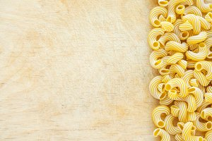 Macaroni rigati Beautiful laid out pasta with the right, side view on a wooden table top with a textured background. Close-up view from the top. Free space for text.