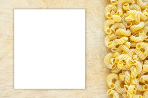 Macaroni rigati Beautiful laid out pasta with the right, side view on a wooden table top with a textured background. Close-up view from the top. White space for text and ideas.