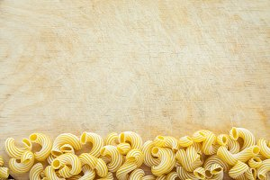 Macaroni rigati Beautiful decomposed pasta with a bottom on a wooden table top with a textured background. Close-up view from the top. Free space for text.