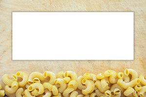 Macaroni rigati Beautiful decomposed pasta with a bottom on a wooden table top with a textured background. Close-up view from the top. White space for text and ideas.