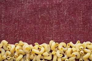 Macaroni rigati Beautiful decomposed pasta from the bottom on a rustic red-brown textured background. Close-up view from the top. Free space for text.