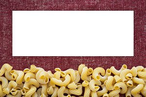 Macaroni rigati Beautiful decomposed pasta from the bottom on a rustic red-brown textured background. Close-up view from the top. White space for text and ideas.