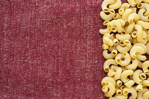 Macaroni rigati Beautiful decomposed pasta with the right, on its side on a rustic red-brown textured background. Close-up view from the top. Free space for text.