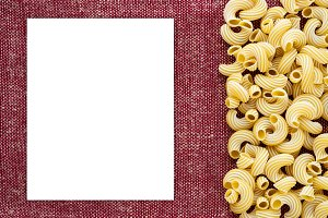 Macaroni rigati Beautiful decomposed pasta with the right, on its side on a rustic red-brown textured background. Close-up view from the top. White space for text and ideas.