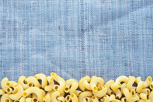 Macaroni rigati Beautiful decomposed pasta with a bottom on a rustic blue knitted sack texture. Close-up view from the top. Free space for text.