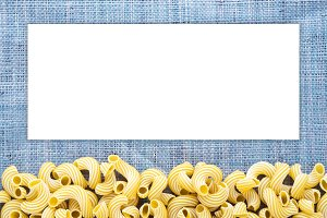 Macaroni rigati Beautiful decomposed pasta with a bottom on a rustic blue knitted sack texture. Close-up view from the top. White space for text and ideas.