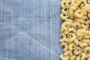 Macaroni rigati Beautiful decomposed pasta with the right, on its side on a rustic blue knitted sack texture background. Close-up view from the top. Free space for text.