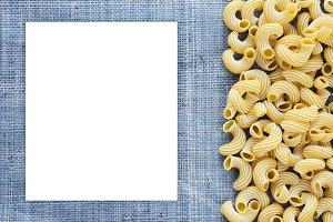 Macaroni rigati Beautiful decomposed pasta with the right, on its side on a rustic blue knitted sack texture background. Close-up view from the top. White space for text and ideas.