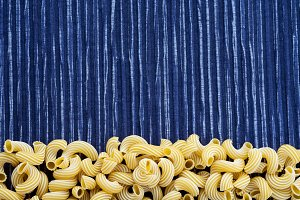 Macaroni rigati Beautiful decomposed pasta with a bottom on a rustic striped blue white textured background. Close-up view from the top. Free space for text.