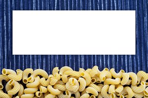 Macaroni rigati Beautiful decomposed pasta with a bottom on a rustic striped blue white textured background. Close-up view from the top. White space for text and ideas.