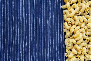 Macaroni rigati Beautiful decomposed pasta with the right, on its side in a rustic striped blue against a white textured background. Close-up view from the top. Free space for text.