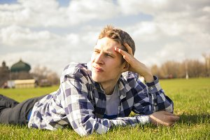 young man lying on the ground dreaming and relaxing against the sky background