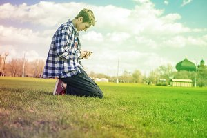 young man in shirt sitting on the grass and speaking phone on a sunny day